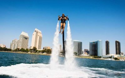 Jetpack by jetpack america shows a girl with a jetpack atop of the water with water shooting out of the pack and a city in the background