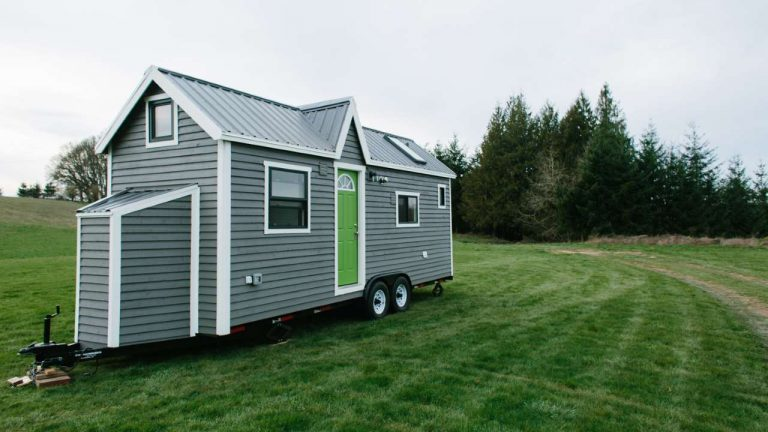 tiny house by tiny heirloom a small grey house in a field with green trees in the background