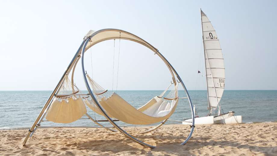hammocks by trinity hammocks on a beach with a sailboat in the background