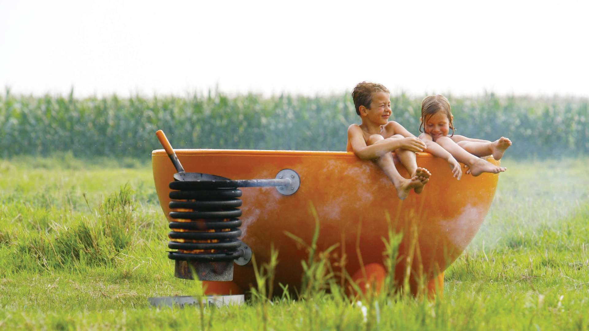 hot tubs by weltevree an orange wood fire hot tub with children in a field with corn stalks in the background