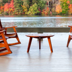 chairs by Brian Boggs Chairmakers chairs and a table on a dock with a river and trees in the background