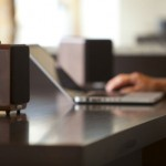 audio by Ruark Audio show to small speakers on a desk with someone looking at a laptop
