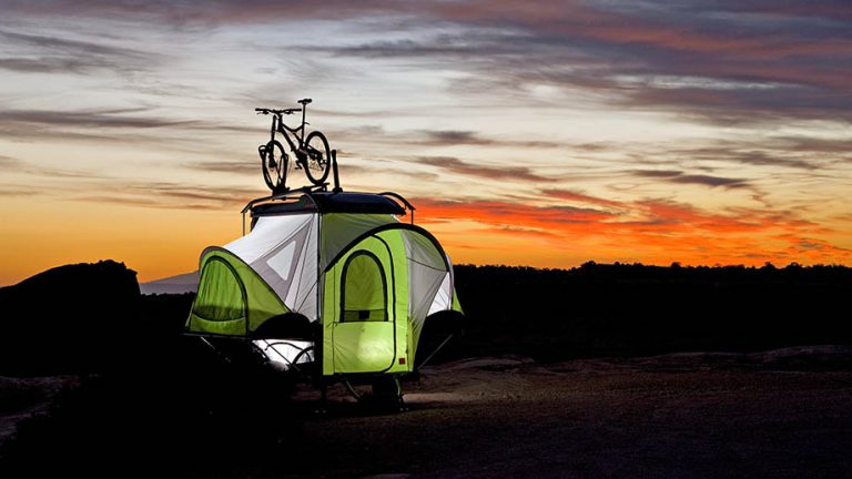 adventure trailers by sylvan sport featuring a green pop up camper in the woods during a sunset