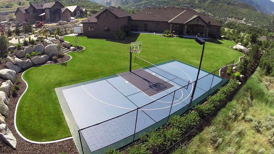athletic surfaces by SnapSports features a basketball court in a rich persons backyard with green grass and a fence