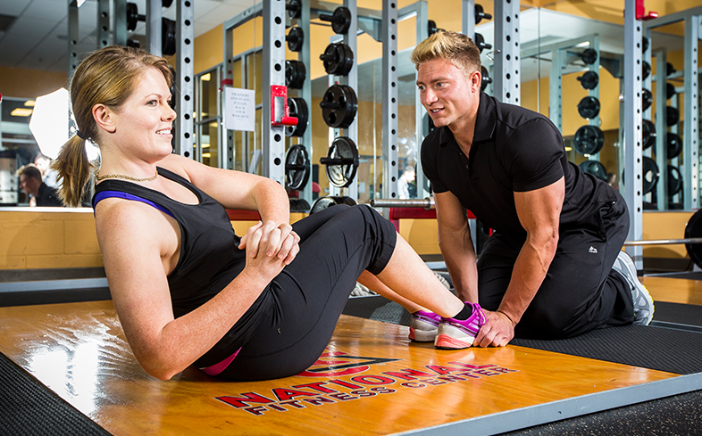 personal trainer features a male trainer teaching a women exercise moves