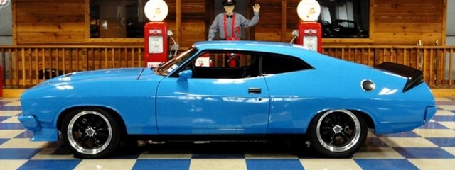 classic cars by a&e classic cars features a blue camaro with a black spoiler in a showroom