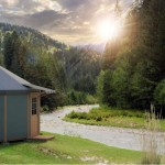 yurt cabin by freedom supply company a grey yurt sitting on a river