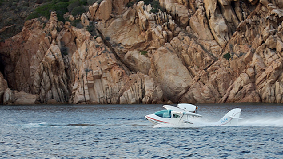 SeaMax amphibious aircraft in a body of water with a cliff in the background