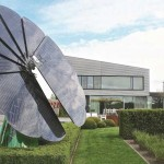 solar energy by Smartflower on a lawn with a luxury house in the background