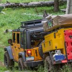 expedition trailers by turtleback a yellow vehicle and trailer driving down a grass covered road