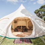 glamping by Lotus Belle tent set up outside with a house and body of water in the background