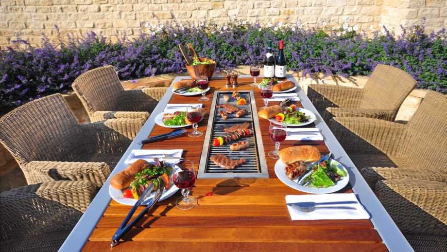 barbecue tables by IBBQ with table settings, chairs and food being barbecued