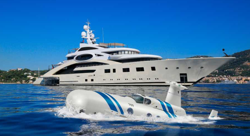 luxury submarines in the ocean next to a yacht in the ocean