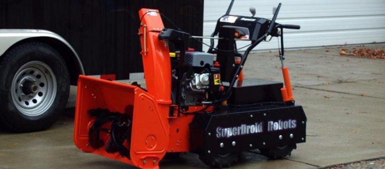 snowblower by robotshop orange and black in the driveway