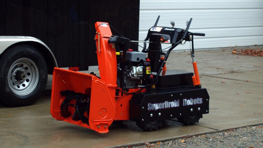 snowblower by robotshop orange and black in the driveway