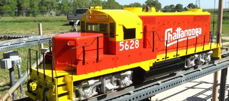 luxury train by Backyard Trains features an orange and yellow train on a backyard tracks