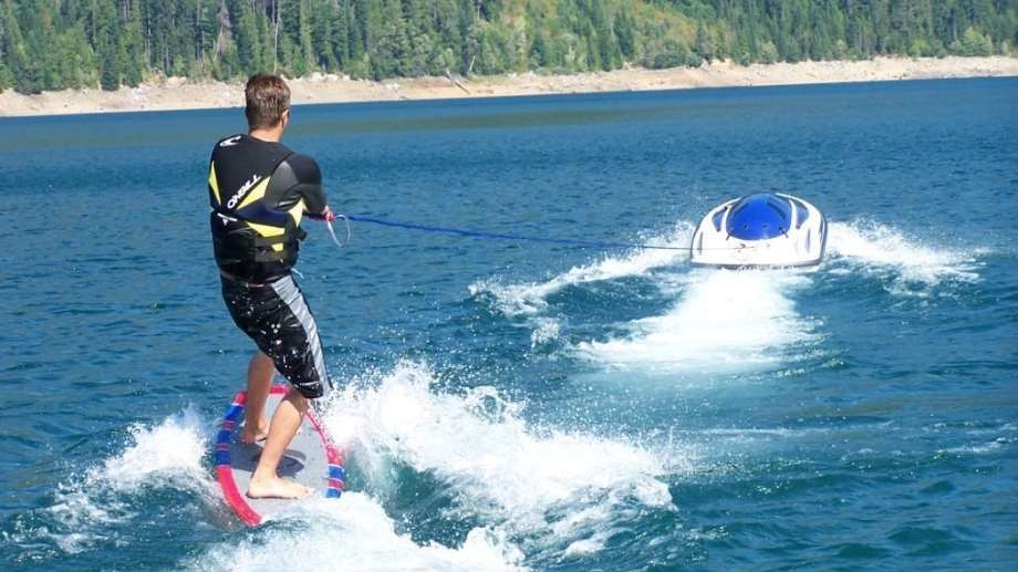 luxury water toy by solo ski machine features man skiing behind the solo on a body of water