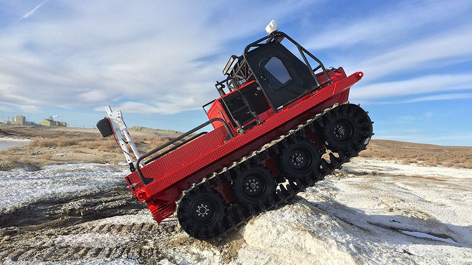Hydratrek ATV shows a red vehicle going over a mound of sand