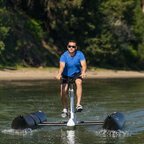 luxury water bike by schiller bikes with someone riding on a lake with a beach